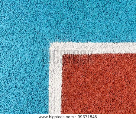 Running track made from red and blue granule rubber and white corner poster