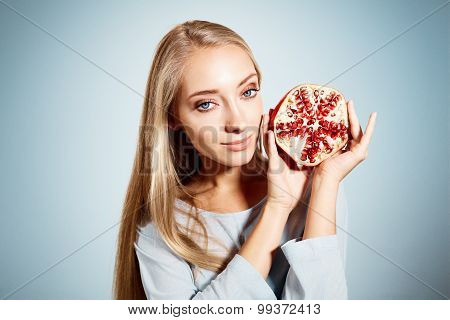Portrait Of Young Beautiful Blonde Woman With Pomegranates In Her Hands Isolated On Blue Background