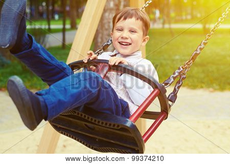 laughing little boy riding on a swing and looking at camera in a park