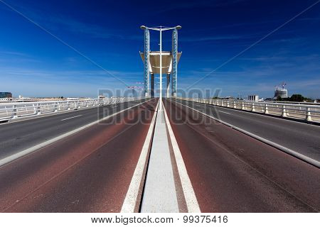 View in the middle of the Jacques Chaban Delmas bridge who is a suspended modern structure with a raising platform to let the ship entering the port of Bordeaux in France.