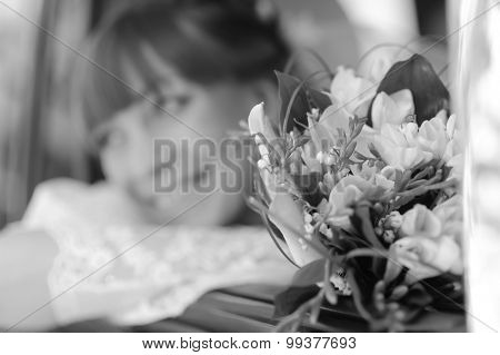 Close up portrait of young woman in wedding dress with bunch of flower. Focus on flowers, woman defocused