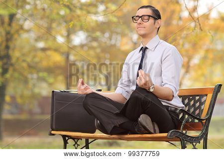 Relaxed young businessman meditating seated on a bench in park