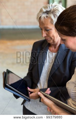 Two Business Women With Tablets In A Warehouse