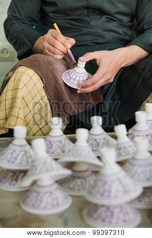 The Artist Paint The Purple Color On The Pottery Cover