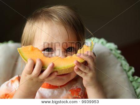 Baby eating cantaloupe fruit