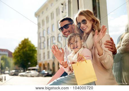 sale, consumerism and people concept - happy family with little child and shopping bags waving hands at shop window in city