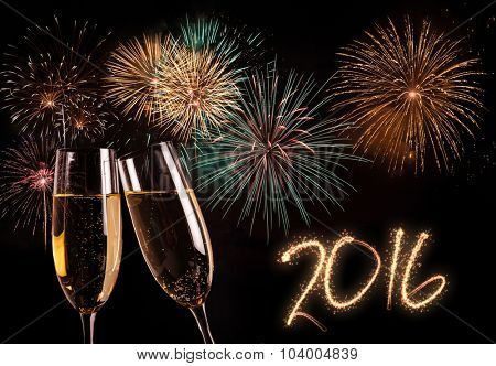 Pair of champagne flutes and fireworks in the background. New year 2016 concept