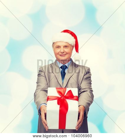 business, christmas, xmas, happiness concept - smiling old man in suit and santa helper hat with gift