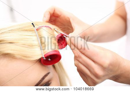 A woman in a hair salon, barber turns hair on rollers