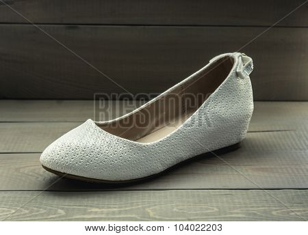 White women shoes on wooden background. Toned photo