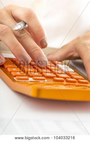 Closeup Of Female Student Hand Calculating Using Orange Desk Calculator