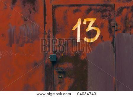Number Thirteen On Red Metal Locked Door.