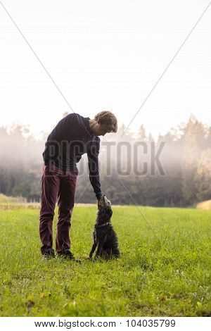 Man Standing Enjoying Nature As He  Bends Down To His Dog To Pat It