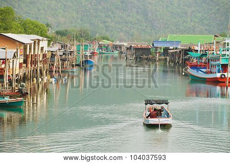 Man rides motorboat by the fishermen village in Sam Roi Yot National park, Sam Roi Yot Thailand.