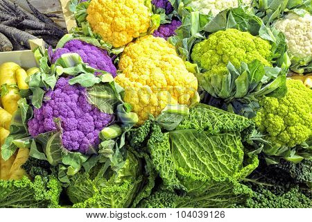 Vegetable display of white green purple cauliflowers and cabbage