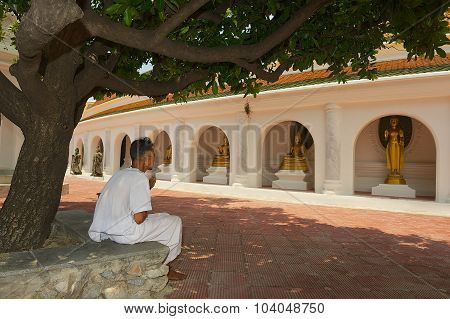 Man prays outside of the temple in Nakhom Pathom, Thailand.