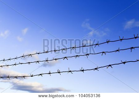 three rows of barbed wire