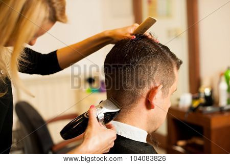 Female hairdresser cutting hair of smiling man client at beauty parlour poster