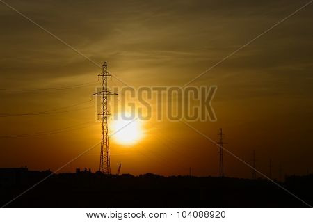 Towers of high voltage power lines in sunset light