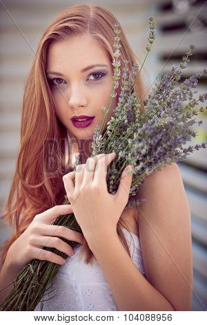 Beautiful Young Woman On Lavender Field holding bouquet of lavanda flowers in her hands