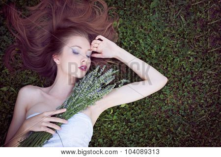 Beautiful young woman lying on lavender field with bouquet of lavanda flowers in her hands