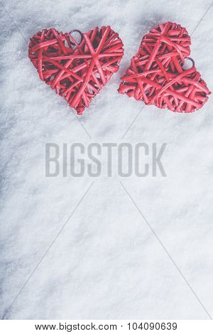 Two beautiful romantic vintage red hearts together on a white snow winter background. Love and St. Valentines Day concept.
