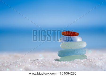 sea glass seaglass stone on glitter sand with ocean , beach and seascape, shallow dof