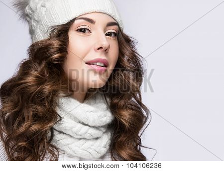 Beautiful girl with a gentle make-up, curls and a smile in winter white knit cap. Warm winter image. Beauty face. Picture taken in the studio. poster