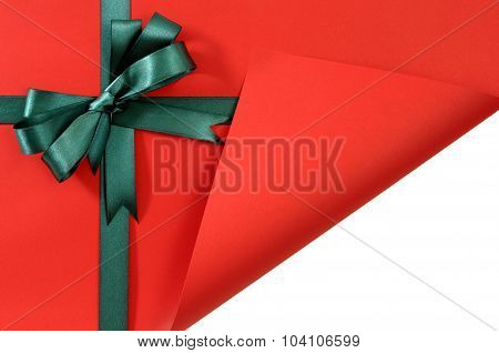 Green Gift Ribbon Bow On Plain Red Background Paper, Corner Folded Open Revealing White Copy Space
