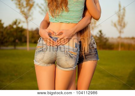 Close-up Photo Of A Girl Showing A Heart With Fingers Upon Her Girlfriend