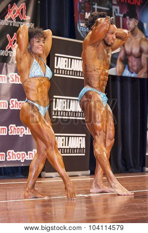 Bodybuilding Duo In Abdominals And Thighs Pose On Stage