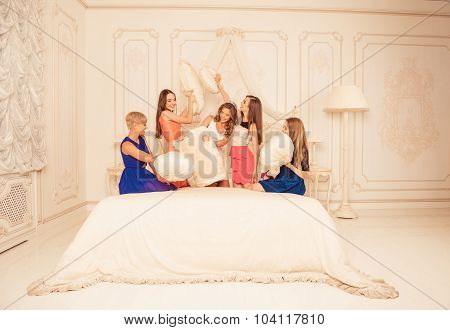 Playful Girls Celebrating A Bride's Bachelorette Party And Fighting With Pillows