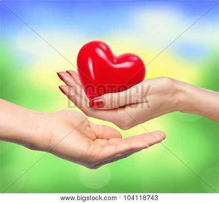 Red Heart In Woman Hand And Man Handover Blurred Nature Background