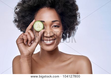 Fun portrait of beautiful black african model with flawless complexion smooth skin holding a cucumber slice to her eye, rejuvenating skin care regime treatment facial beauty concept