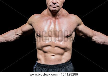 Midsection of fighter with arms outstretched against black background