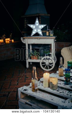 White star lamp with light bulbs over wooden cart