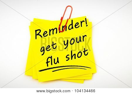 Flu shot reminder against sticky note with red paperclip