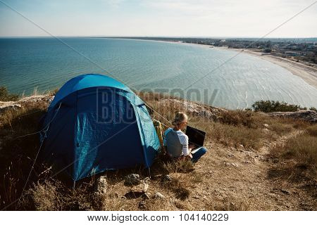 Happy Woman Sitting Near Tent With Laptop, View Of Mountains ,sky And Sea