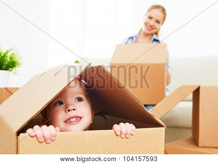 Happy Family Moves Into A New Apartment. Happy Baby In A Cardboard Box