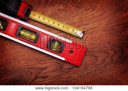 Tape Measure And Building Level On Wooden Background