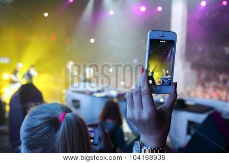MOSCOW, RUSSIA - NOVEMBER 15, 2014: Female hand with telephone relieves concert at a party Diskach 90th in a club Space Moscow