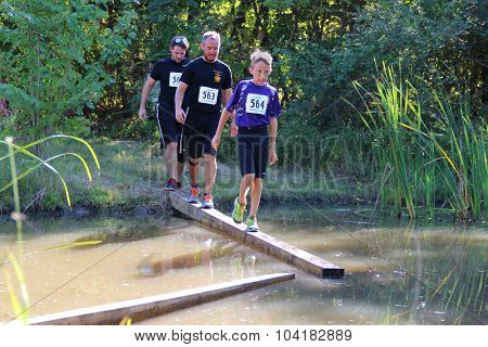 MUSKOGEE, OK - Sept. 12: Athletes go through mud and water to avoid bloody zombies during the Castle Zombie Run at the Castle of Muskogee in Muskogee, OK on September 12, 2015.