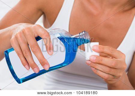 Woman Pouring Mouthwash Into Bottle Cap