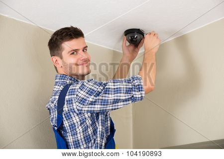 Young Male Technician Installing Surveillance Camera On Ceiling poster