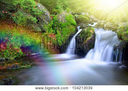 Waterfall on a mountain creek with rainbow.