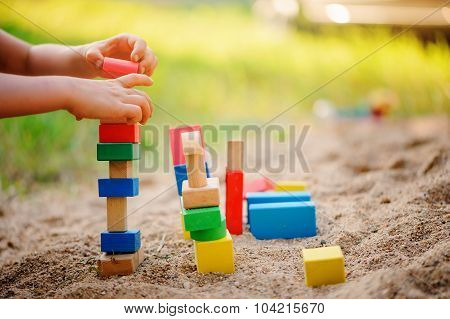 child building toy houses of colorful wooden bricks in sandbox