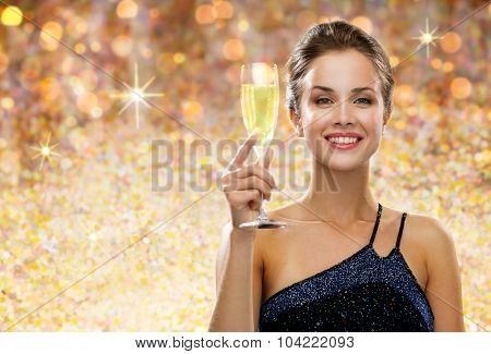 party, drinks, people, luxury and celebration concept - smiling woman in evening dress with glass of champagne over golden holidays lights background