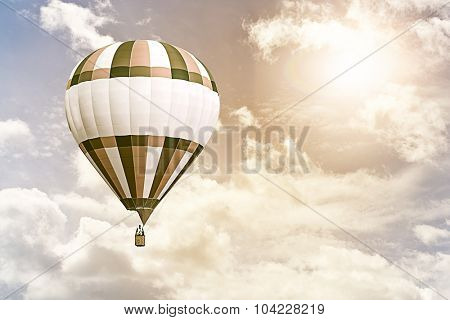 hot air balloon flying through a cloudy sky against the sun
