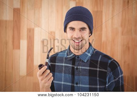 Portrait of happy hipster holding smoking pipe against wooden wall in office