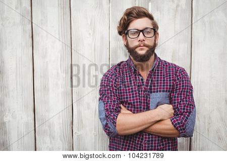 Confident hipster wearing eye glasses with arms crossed standing against wooden wall